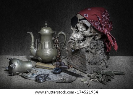 Still life, pirate skull with cigar in the mouth on the log, compass on ancient map, brass tea pots knife and pocket  - stock photo