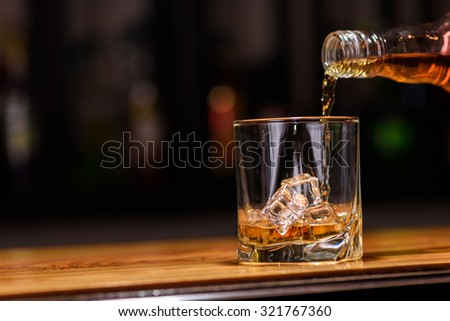 Still life. pour or whiskey in to glass. - stock photo