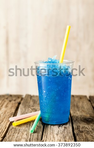 Still Life Profile of Refreshing and Cool Frozen Blue Fruit Slush Drink in Plastic Cup Served on Rustic Wooden Table with Colorful Drinking Straws - stock photo