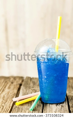 Still Life Profile of Refreshing and Cool Frozen Blue Fruit Slush Drink in Plastic Cup with Lid Served on Rustic Wooden Table with Colorful Drinking Straws - stock photo