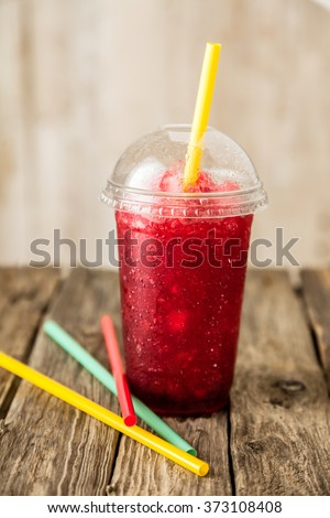 Still Life Profile of Refreshing and Cool Frozen Red Fruit Slush Drink in Plastic Cup with Lid Served on Rustic Wooden Table with Collection of Colorful Straws - stock photo