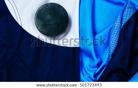 Still life puck on a dark blue and white jersey as a sport background. Ice hockey season concept closeup, top view.