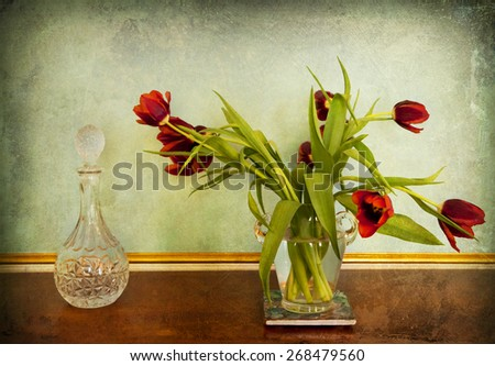 Still life, red tulips in glass vase and decorated glass bottle in interior on grunge vintage background - stock photo