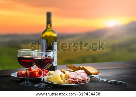 still life Red wine  ,cheese and prosciutto. Romantic dinner  outdoors - stock photo