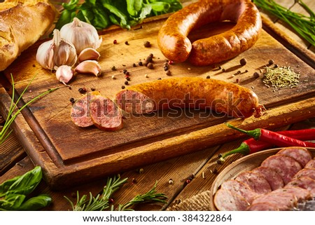 Still life - sausage with greens on the board isolated on a wooden background