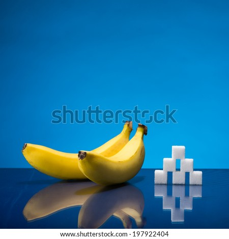 Still life showing amount of sugar in two bananas - stock photo