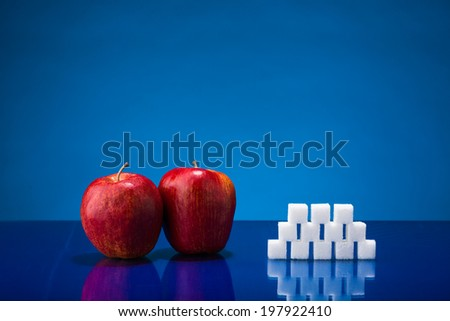 Still life showing amount of sugar in two red apples - stock photo