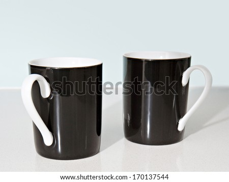 Still life side view of two black and white tea mugs aligned together on a kitchen counter. Home interior coffee drinking detail. - stock photo