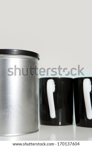 Still life side view of two black and white tea mugs together on a kitchen counter with a silver jar. Home interior coffee drinking detail. - stock photo