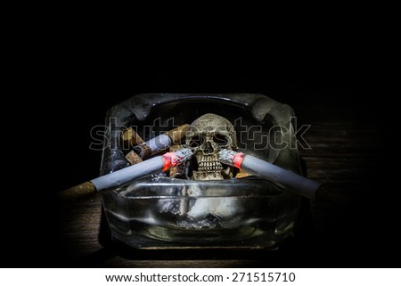 "Still life skull and cigarette in glass ashtray. people  smoke and get toxin in body look like go to way to die.In the day "" World No Tobacco Day"" please  quit smoke cigarette for  good health. - stock photo"