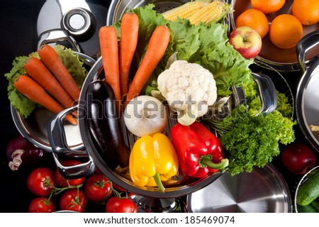 Still Life: stainless steel set of kitchen utensils, on a red background with vegetables and fruit - stock photo