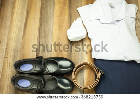 Still life : Thai Student girl uniform with wooden background on top view