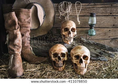 still life three human skull on hay with traditional leather boots and american west rodeo brown felt cowboy hat background, vintage and dark tone for horror halloween - stock photo