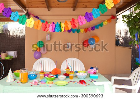 Still life view of a children birthday party table decorated with fun and colorful deco and balloons in a home garden space, outdoors. Kids party decorations and fun activities space, home exterior.