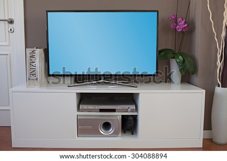 Still life view of a large home entertainment flat screen tv in a modern high technology house, interior. Elegant luxurious quality home cinema smart television with a blue screen, stylish indoors. - stock photo