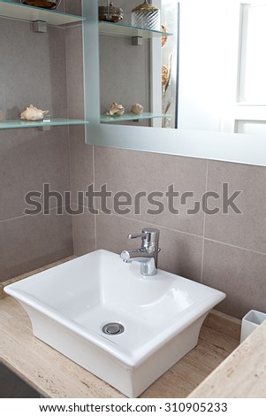 Still life view of a new white sink with silver tap in a stylish bathroom in a quality design home, interior. Bath room and washing facilities in a hotel room, travel and aspirational lifestyle.