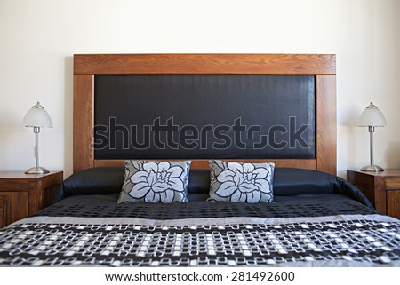 Still life view of an apartment masculine bedroom with wooden furniture in a bright home interior. Comfortable bed room view with a wood and black headboard, house interior and home living detail. - stock photo