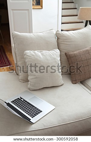 Still life view of luxury living room with white sofa with cushions and with open laptop computer, quality home interior. Aspirational high end technology, indoors lifestyle. Spacious home living. - stock photo