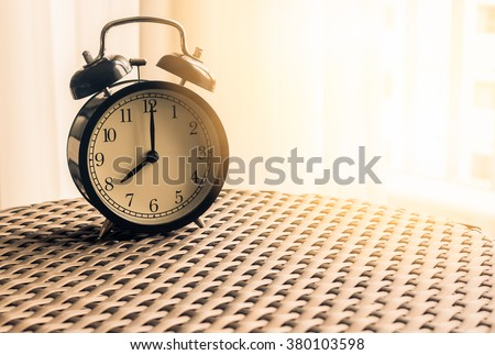 Still life , vintage alarm clock on weave table with sunlight ( alarm clock show 8 o`clock ) - stock photo