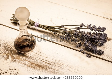 Still life vintage picture, old perfume bottle and a bunch of dried lavender. - stock photo