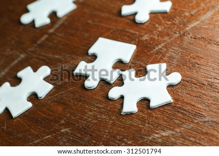 Still life white jigsaw puzzle in wood background.