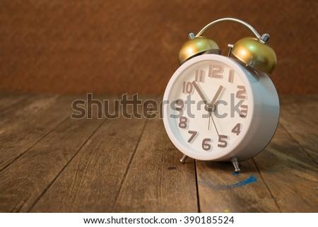 still life white retro clock on wooden table - stock photo