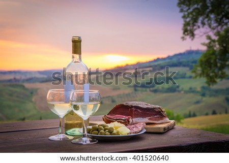 still life White wine  ,cheese and prosciutto. Romantic dinner  outdoors - stock photo