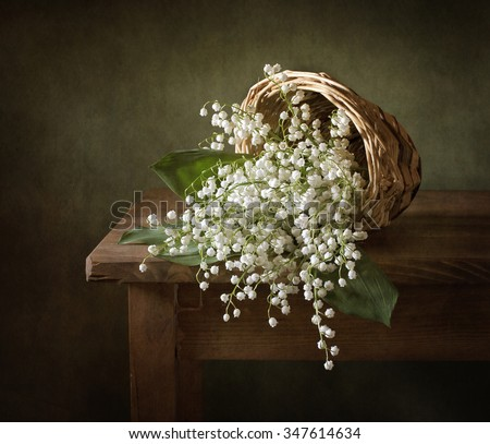 Still life with a basket full of lilies of the valley (textured for artistic effect) - stock photo