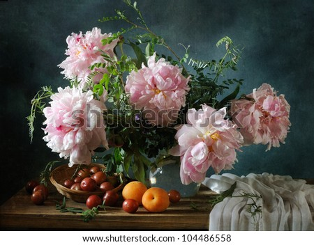 Still life with a beautiful bouquet of peonies and fruit - stock photo