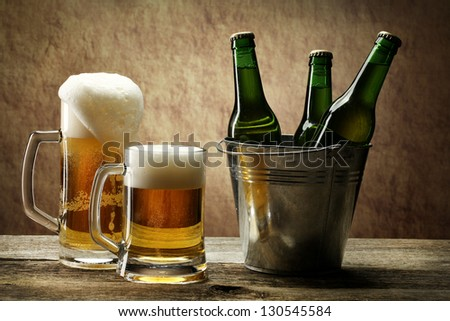 Still Life with a  beer in the mug and bottles of beer in basket - stock photo