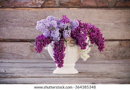 Still life with a blooming branch of lilac - stock photo