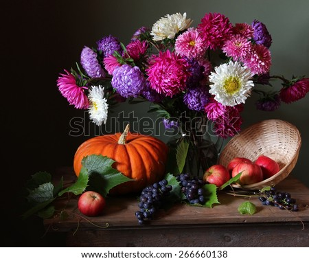 still life with a bouquet of asters, apples, grapes and pumpkin against a dark background - stock photo