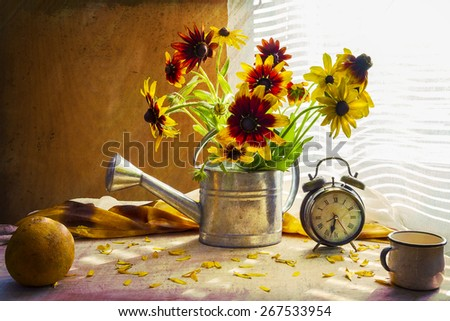 Still life with a bouquet of yellow rudbeckia in a watering can and a clock - stock photo