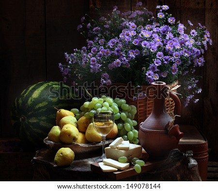 Still-life with a bright bouquet, juicy ripe appetizing fruit and a glass of fragrant white wine - stock photo