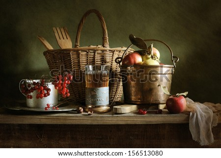 Still life with a bucket of apples and a cup of tea - stock photo