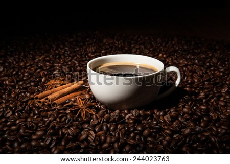 Still-life with a cup of black coffee and roasted coffee beans close up