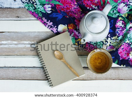 still life with a cup of tea with teapot and note book on wooden table.flat lay.(selective focus) - stock photo