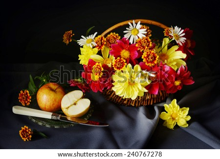 Still life with a cut apple and beautiful flowers into the basket - stock photo