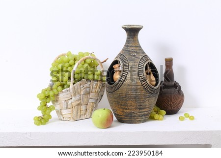 Still-life with a decorative wine jug and juicy sweet green grapes in a wattled basket and a fragrant apple - stock photo