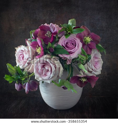 Still life with a fresh roses in a vase on a dark brown wooden background . - stock photo