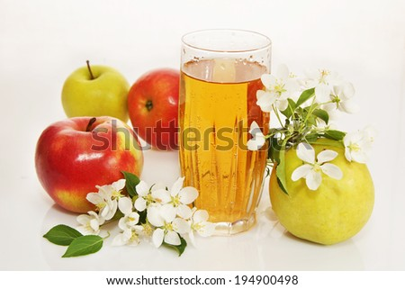 Still life with a glass of fresh apple juice and ripe apples - stock photo