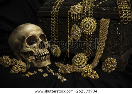 Still life with a human skull with old treasure chest and gold and jewelry - stock photo