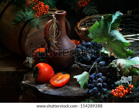 Still-life with a jug for wine a ripe persimmon and sweet grapes, clusters of dark dark blue grapes and a ripe sweet tasty persimmon - stock photo