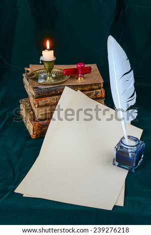Still life with a letter, a pen, a lighted candle in copper candlestick and a pile of old books on a background of dark green velvet - stock photo