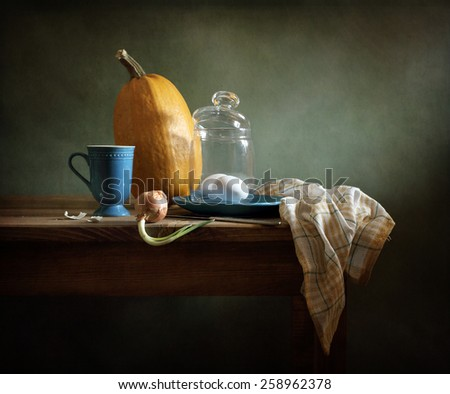 Still life with a pumpkin, eggs and onions - stock photo