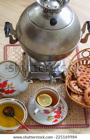 Still-life with a round samovar and fragrant fresh tea with a juicy lemon submitted with fragrant honey and appetizing cookies
