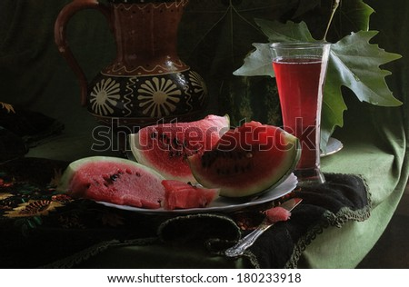 Still-life with a water-melon, a juicy ripe bright red water-melon and fresh sweet water-melon juice in a transparent glass - stock photo