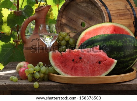 Still-life with a water-melon and fruit, a ripe juicy sweet water-melon and red apples with clusters of juicy appetizing green grapes - stock photo