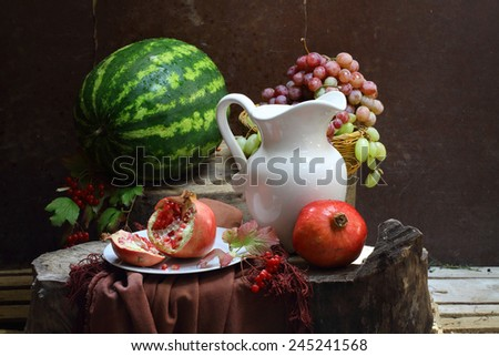 Still-life with a white jug, a pomegranate, grapes and a water-melon - stock photo