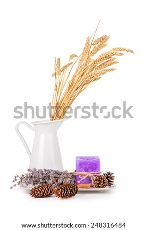 Still life with a white jug and a plate with dry lavender flowers and a lavender candle isolated on white - stock photo